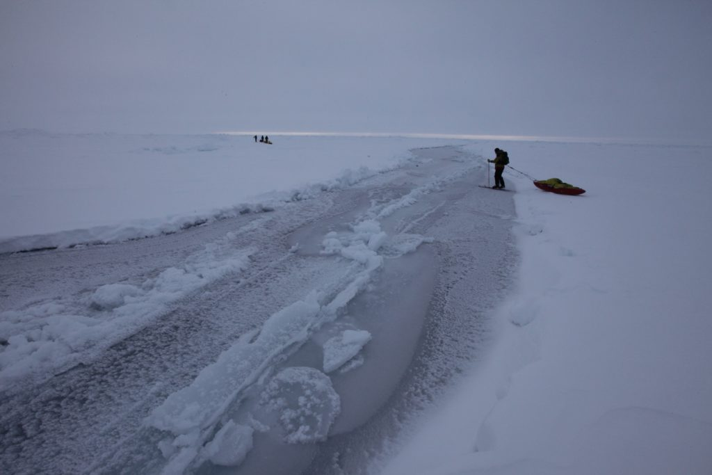 Skier crossing partially frozen open lead at North Pole.